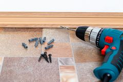 Installation of plastic floor plinth. Interior details. Close up electric drill and nails left on wooden floor. Installation of plastic floor plinth royalty free stock photos