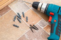 Installation of plastic floor plinth. Interior details. Close up electric drill and nails left on wooden floor. Installation of plastic floor plinth stock photography