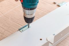 Installation of plastic floor plinth. Interior details. Close up electric drill and nails left on wooden floor. Installation of plastic floor plinth stock photos