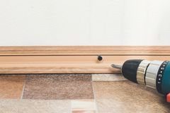 Installation of plastic floor plinth. Interior details. Close up electric drill and nails left on wooden floor. Installation of plastic floor plinth royalty free stock image