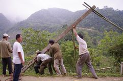Installation of pole. At the roadside stand men of concrete poles for laying electrical and telephone line. Nine men are needed for this dangerous operation. As Stock Photos
