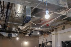 Installation and repair of frame, ventilation system, fire alarm, electric cable, lamp bulb before assembling stretch or suspended. Ceiling. Concept of royalty free stock photography