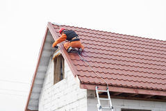 Installation of a roof. Builder performs installation gable roof tiles of metal royalty free stock photos