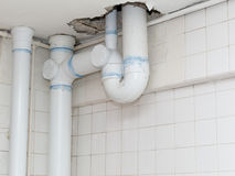 Installation of sanitary pipes. Installation of new sanitary pipes through hole in ceiling inside house under renovation Stock Photos
