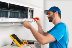 Free Installation Service Fix  Repair Maintenance Of An Air Conditioner Indoor Unit By Cryogenist Technican Worker With Screwdriver Stock Photo - 152179350