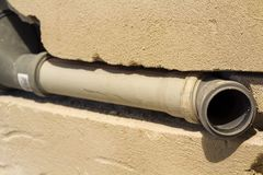 Installation of sewer pipes in a bathroom of an apartment interior during renovation works. Gray plastic drain pipe for used water.  Stock Photo