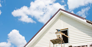 Installation of a siding on a house. Against the sky Royalty Free Stock Photo