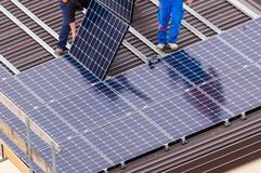 Solar panel and workers. royalty free stock photography