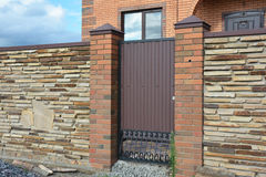 Installation of Stone Fence with Metal Door, Gate royalty free stock photos
