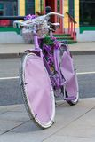 Installation from a vintage pink bike with flowers in basket. Against a city street stock photography