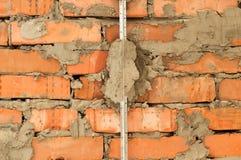 Installation von Metallleuchttürmen auf einer Backsteinmauer Lizenzfreie Stockbilder