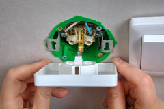 Installation of wall socket in the junction box, hands closeup. Stock Image