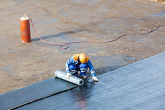 Installation of waterproofing flat roof repair. Professional installation of waterproofing on the concrete foundation. Two worker at construction site royalty free stock image