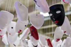 Installation of white, black and red masks stock image