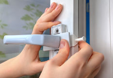 Installation of window restrictor to windows, using your hands, Stock Image
