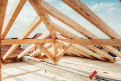 Installation of wooden beams at house construction site. Building details with wood, timber and iron holders. Installation of wooden beams at house construction royalty free stock image