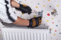 Installazione del radiatore del riscaldamento immagine stock