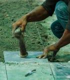 Installazione della piastrella per pavimento del lavoratore dell'uomo della costruzione Immagini Stock