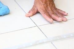 Installazione della piastrella per pavimento per la costruzione di casa Immagini Stock