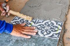 Installazione della piastrella per pavimento per la costruzione di casa fotografia stock