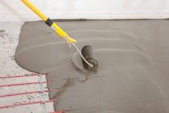 Installazione elettrica del sistema di riscaldamento del pavimento in nuova casa Il lavoratore allinea il cemento con il rullo Immagine Stock
