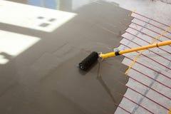 Installazione elettrica del sistema di riscaldamento del pavimento in nuova casa Il lavoratore allinea il cemento con il rullo Fotografia Stock Libera da Diritti