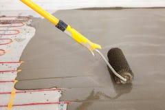 Installazione elettrica del sistema di riscaldamento del pavimento in nuova casa Il lavoratore allinea il cemento con il rullo Fotografia Stock