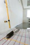 Installazione elettrica del sistema di riscaldamento del pavimento in nuova casa Il primo piano del rooler per allinea il calcest Immagine Stock Libera da Diritti