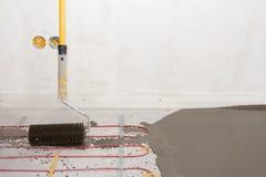 Installazione elettrica del sistema di riscaldamento del pavimento in nuova casa Il primo piano del rooler per allinea il calcest Fotografie Stock Libere da Diritti