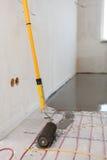 Installazione elettrica del sistema di riscaldamento del pavimento in nuova casa Il primo piano del rooler per allinea il calcest Fotografia Stock Libera da Diritti