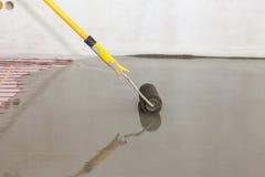 Installazione elettrica del sistema di riscaldamento del pavimento in nuova casa Rullo per il versamento del pavimento di calcest fotografie stock libere da diritti