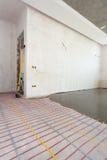 Installazione elettrica del sistema di riscaldamento del pavimento in nuova casa Stanza con le pareti bianche, il cemento ed i ca immagini stock