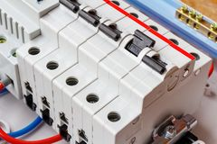 Installed automatic circuit breakers on DIN rail in white plastic mounting box closeup stock photo