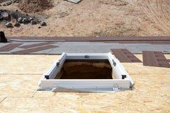 Installed frame of new plastic mansardor skylight  window  on a asphalt shingle roof. Royalty Free Stock Photo