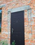 Installeer de deur van de metaalingang in de nieuwe bouw van het baksteenhuis royalty-vrije stock foto