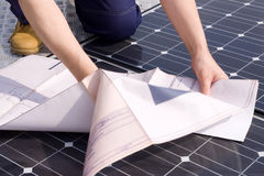 Installer. Worker fitting solar panels on a roof Royalty Free Stock Images