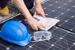 Installer. Worker fitting solar panels on a roof Stock Photo