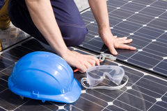 Installer. Worker fitting solar panels on a roof Royalty Free Stock Image
