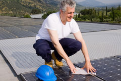 Installer. Worker fitting solar panels on a roof Stock Photos