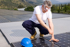Installer. Worker fitting solar panels on a roof Stock Photography
