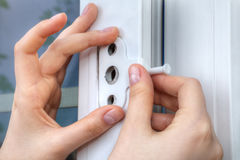 Installer hands close-up, installation of limiter pvc window. Close-up of the hand of a locksmith installing a window limiter on a plastic frame Stock Photos