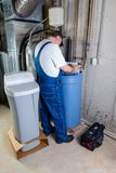 Installer inputting settings on a water softener. Installer inputting the settings on a new replacement water softener that he has just installed in a basement Stock Photo