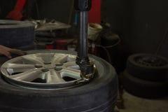 Installera ett nytt bilhjul på däckborttagningsmedelmaskinen Arkivfoto