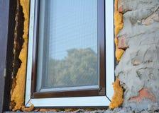 Installera fönsterisolering med skum Fönster för en mygga förtjänar erbjudandeskydd royaltyfria foton