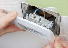 Installera mellanlägget för den ljusa strömbrytaren för väggen in i den elektriska asken royaltyfri foto