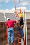 installera sol- arbetare för paneler Arkivfoton