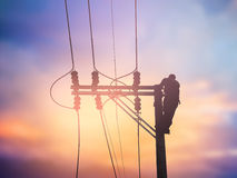 Installeren de silhouet elektroarbeiders hoogspanningssysteem Stock Foto
