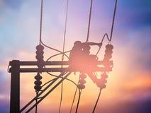 Installeren de silhouet elektroarbeiders hoogspanningssysteem Stock Afbeeldingen
