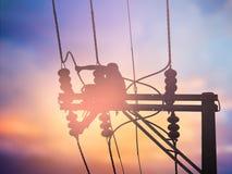 Installeren de silhouet elektroarbeiders hoogspanningssysteem Stock Afbeelding