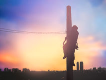 Installeren de silhouet elektroarbeiders hoogspanningssysteem Stock Foto's